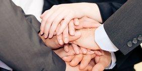 6 Hände sind aufeinander gelegt